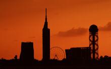 Silhouette Skyscrapers And Ferris Wheel Against Orange Sky