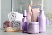 Set Of Hair Care Cosmetic Products Covered With Water Drops On Light Grey Stone Table In Bathroom