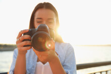 Young Photographer Taking Picture With Professional Camera Outdoors