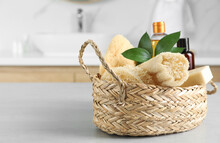 Natural Loofah Sponges In Wicker Basket On Table Indoors. Space For Text