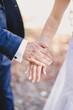 Groom holds bride hand in white dress