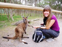 Portrait Of Smiling Young Woman With Kangaroo Crouching On Footpath