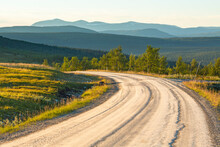 Curve On A Dirt Road With A Scenic View Of A Forest Landscape With The Mountains On The Horizon