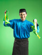Leinwandbild Motiv Man In Traditional Clothing Holding Decorations Against Green Background