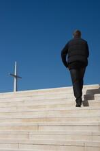 Verso La Fede , Cielo Azzurro Intenso , Con Uomo Vestito Di Nero Che Va Verso L'alto Verso La Croce Di Marmo Sulle Scale Chiare