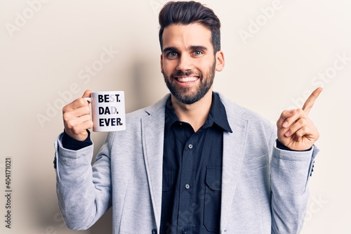 Valokuvatapetti Young handsome man with beard drinking mug of coffe with best dad ever message s