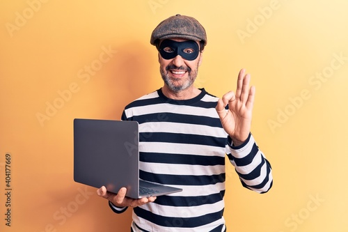 Stampa su Tela Middle age handsome burglar man wearing cap and mask using laptop over yellow ba