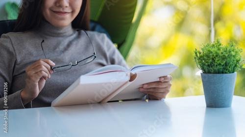 Fototapeta Closeup image of a beautiful young asian woman holding eye glasses while reading
