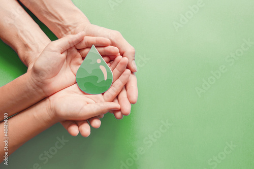 Obraz Hands holding paper cut green oil drop, CSR, alternative biofuel renewable green energy concept - fototapety do salonu