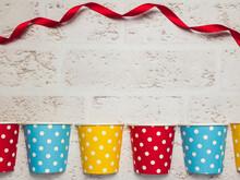 水玉模様のパーティ用紙コップと赤いリボン