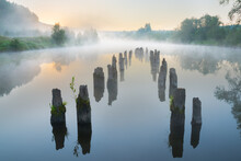 Misty Morning On The River. Calm Water And The Remains Of An Old Pier