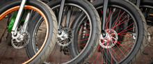 Vintage Bicycles In A Parking Lot At A Store Or Rental. A Close-up Of The Front Wheels Of A Disc Brake Bicycle. Wide