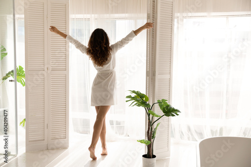 Fotografia Back view of happy young woman in bathrobe open curtains look in window in cozy living room meet new sunny day