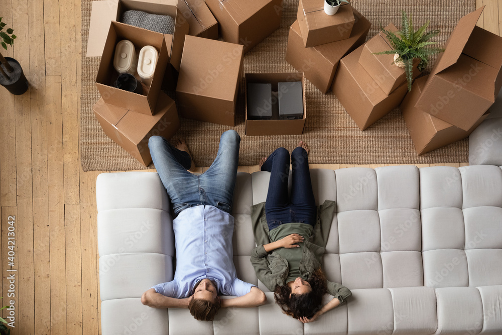 Fototapeta Top view of millennial couple relax on comfortable modern couch feel tired on moving day to new home. Man and woman renters or tenants rest on sofa in living room exhausted with relocation.