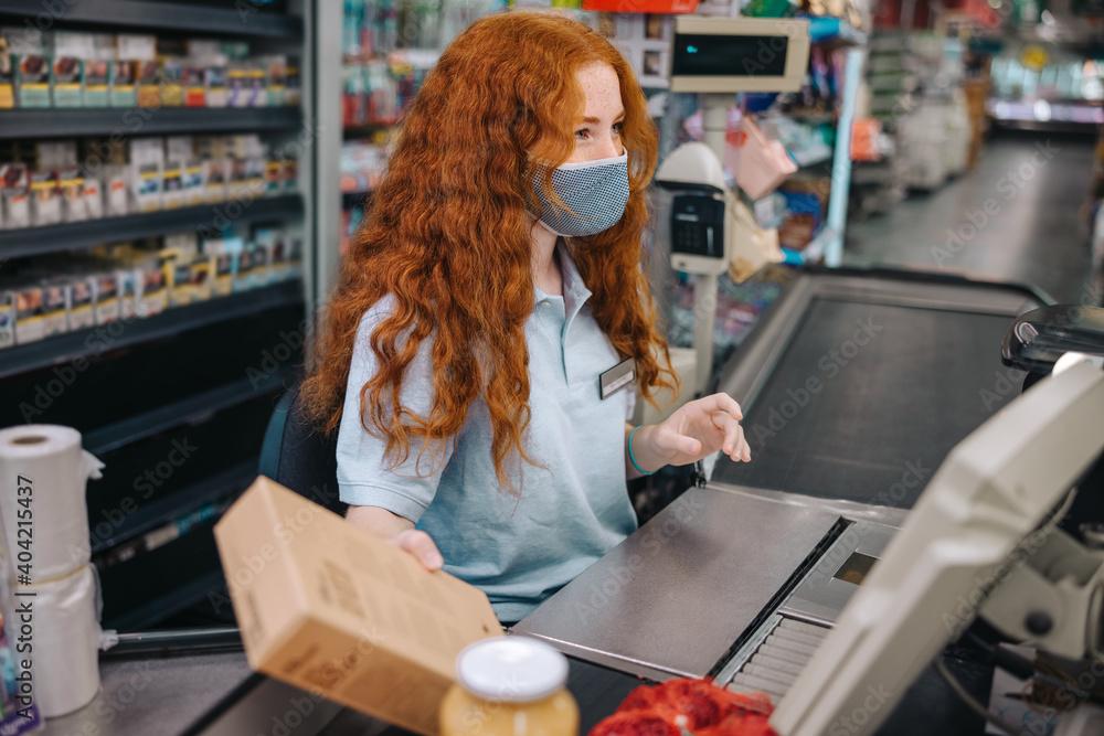 Fototapeta Supermarket cashier with face mask