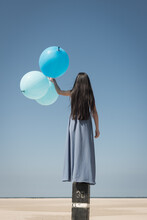Girl In Classic Long Blue Dress With Three Large Blue Balloons On Beach Near Ocean