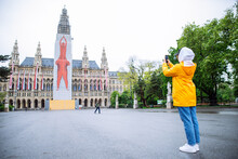 Vienna, Austria - May 16, 2019: Female Woman Tourist In Yellow Raincoat Posing In Front Of City Hall Building