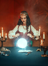 Fantasy Beautiful Gypsy Girl, Predicts Fate, Feel Energy Of Crystal Ball In Dark Gothic Room. Mystical Photo Of Old Art Vintage Astrology. Fortune Teller Woman Reading Future On Magical Tarot Cards