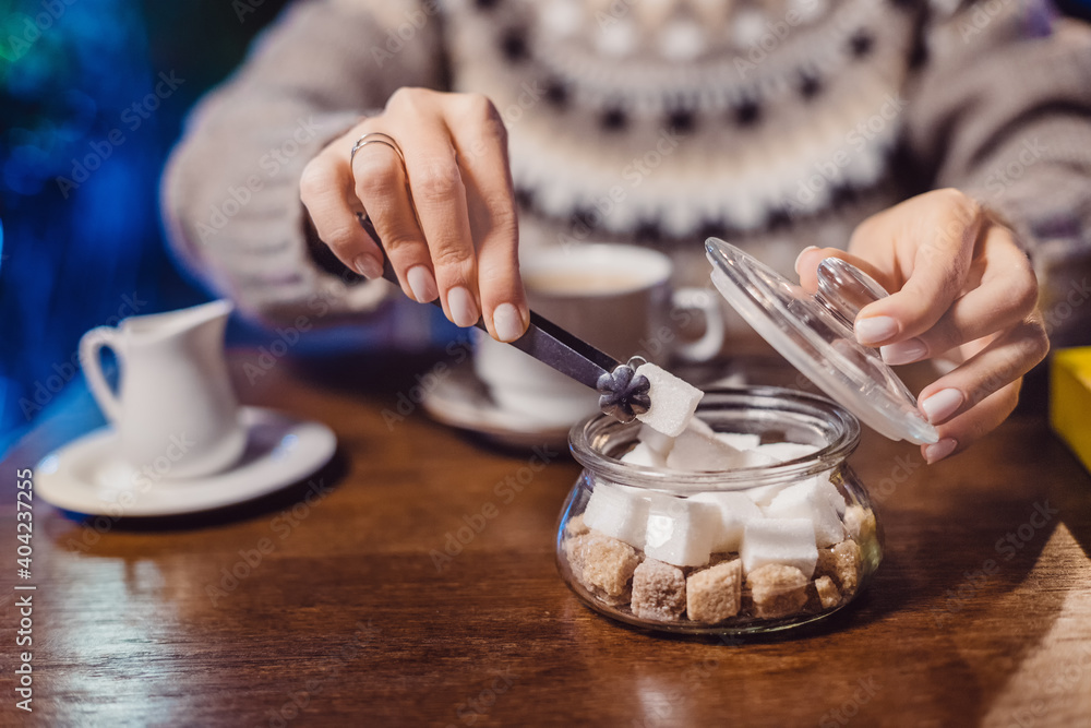 Fototapeta An addicted coffee lover puts a piece of white sugar in his hot drink in cafe. Concept of unhealthy diet and diabetes