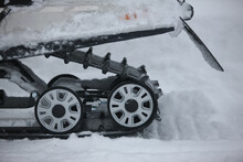 Rear Rollers Of A Snowmobile On A Caterpillar On A Background Of Snow View Outdoor.