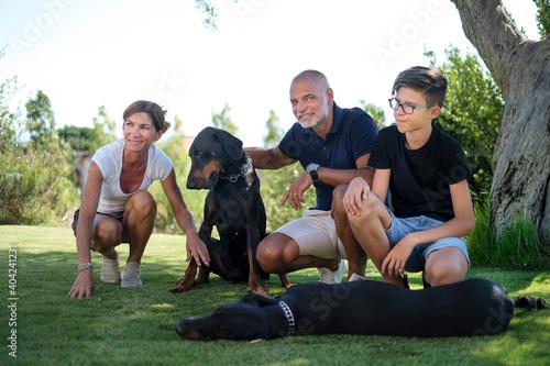 Fotografie, Obraz Bella famiglia con i cani, sorride felice nel prato del giardino di casa