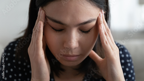 Close up headshot front view unhappy upset millennial korean vietnamese woman massaging temples, having painful feelings or trying coping with stress bad mood, suffering from psychological problems.