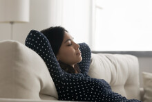 Side View Relaxed Young Asian Korean Woman Daydreaming Napping Leaning On Comfortable Couch, Enjoying Peaceful Stress Free Lazy Leisure Weekend Time In Living Room, Meditating With Close Eyes.