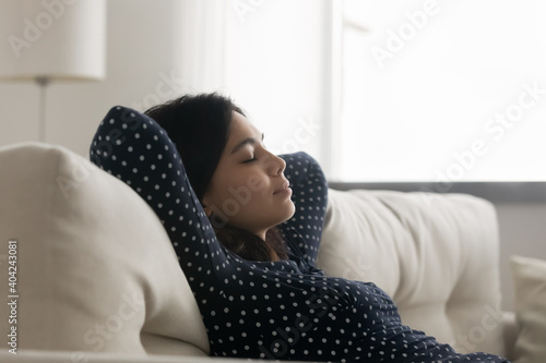 Obraz Side view relaxed young asian korean woman daydreaming napping leaning on comfortable couch, enjoying peaceful stress free lazy leisure weekend time in living room, meditating with close eyes. - fototapety do salonu