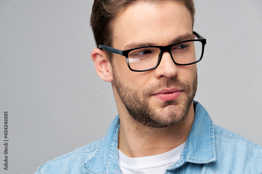 Fototapeta Close-up Portrait of young handsome caucasian man in jeans shirt over light background