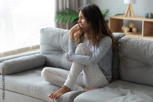 Obraz Frustrated unhappy woman crying, sitting on couch at home alone, thinking about personal problem, break up with boyfriend or divorce, need psychological help, feeling lonely and depressed - fototapety do salonu
