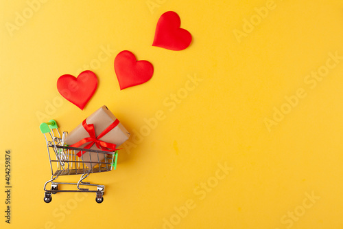 Fotomural Gift box with red ribbon inside mini grocery cart, red hearts on yellow backgrou