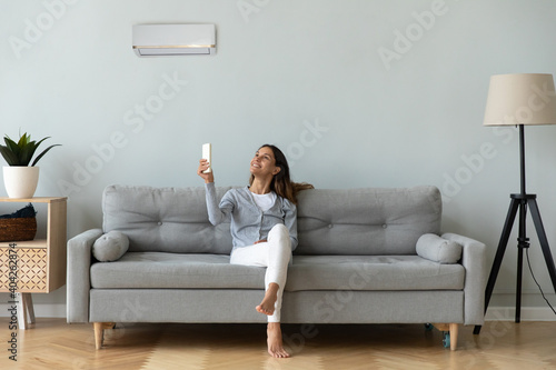 Fotografía Smiling woman using air conditioner remote controller, sitting on cozy couch at
