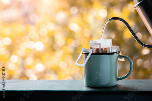 Obraz Dripping Coffee Outdoor in the Morning. Making Hot Drink by Instant Coffee Drip Bag. Cozy Living Lifestyle - fototapety do salonu