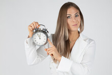 Young Female Businesswoman Demonstrating Alarm Clock Showing Almost Midnight Time While Standing Against White Background