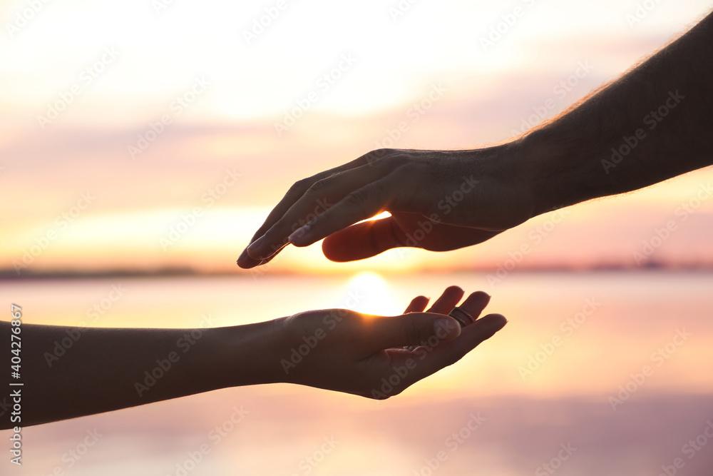 Fototapeta Man and woman reaching hands to each other at sunset, closeup. Nature healing power