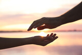 Man and woman reaching hands to each other at sunset, closeup. Nature healing power