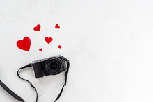 Retro Photo Camera With Red Hearts On A Light Background. Travel Concept.