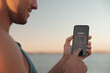 Man using fitness app on smartphone near river at sunset, closeup