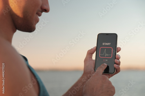 Photo Man using fitness app on smartphone near river at sunset, closeup