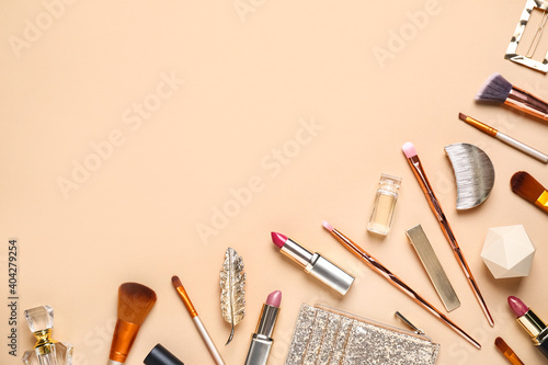 Obraz na plátně Makeup brushes and cosmetic products on beige background, flat lay