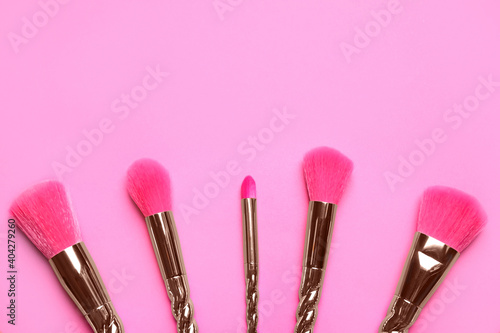 Fotografie, Obraz Set of makeup brushes on pink background, flat lay