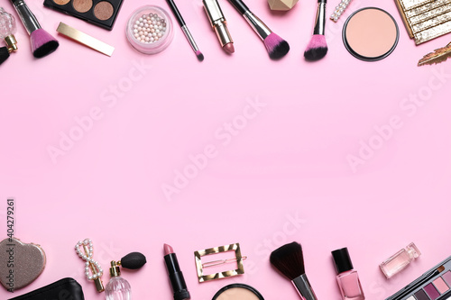 Fototapeta Makeup brushes and cosmetic products on pink background, flat lay