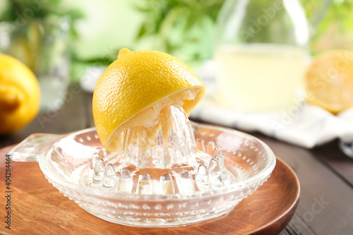Glass citrus squeezer with lemon half on wooden plate