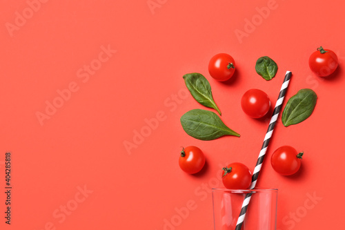 Cherry tomatoes, spinach leaves and glass with straw on coral background, flat lay. Space for text