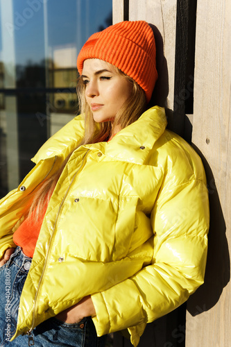 Canvas Print Stylish girl wearing yellow puffer and orange knitted hat