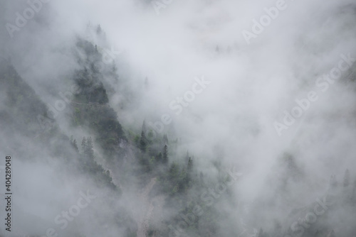 Fotografering Mist in the mountains of the Bavarian alps near Garmisch Partenkirchen with some barely visible trees no