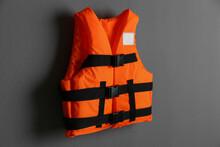 Orange Life Jacket On Grey Background. Personal Flotation Device