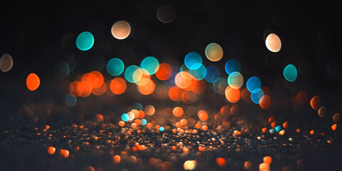Background abstract glitter lights blue and orange on black defocus. Beautiful banner colored bokeh.
