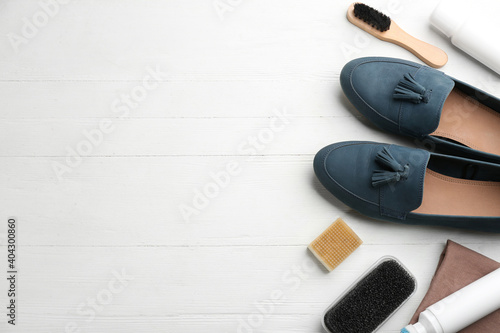 Obraz Stylish footwear with shoe care accessories on white wooden table, flat lay. Space for text - fototapety do salonu