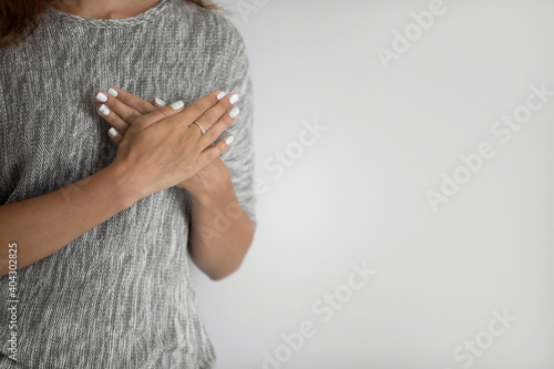 Foto Crop close up of woman isolated on grey studio background hold hands at chest praying to God